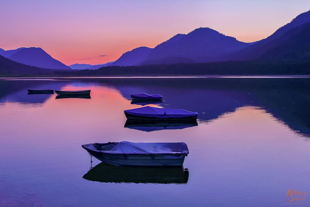 Abendstimmung am Sylvensteinsee mit Fischerbooten.