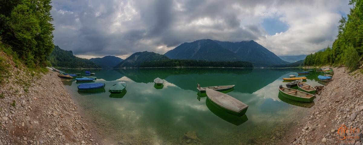 Sylvensteinsee mit Fischerbooten an einem bewölkten Sommervormittag als Pano.