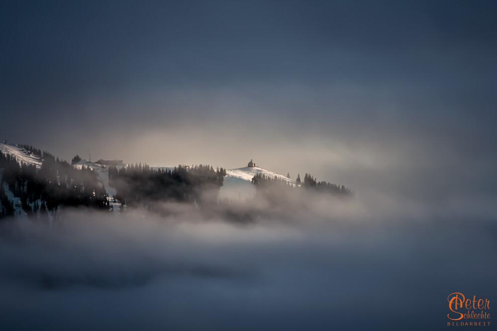 Wallberggipfel am Tegernsee mit Kapelle in Wolken.