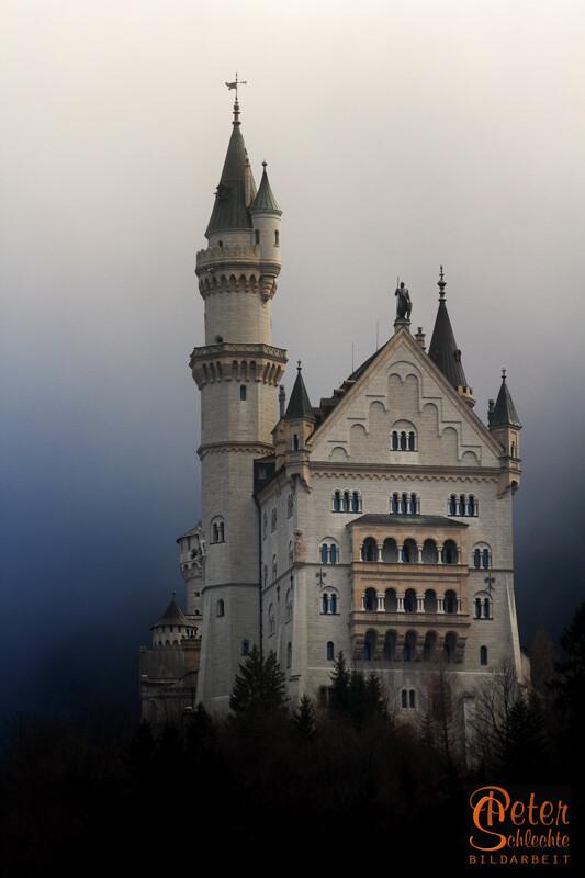 Frontansicht von Schloß Neuschwanstein im morgendlichen Nebel.