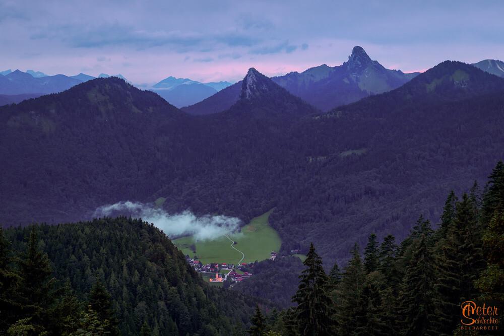 Kreuth in der Abenddämmerung mit Leonhardstein im Hintergrund.