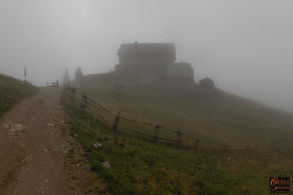 Das Rotwandhaus überhalb vom Spitzingsee im herbstlichen Nebel.