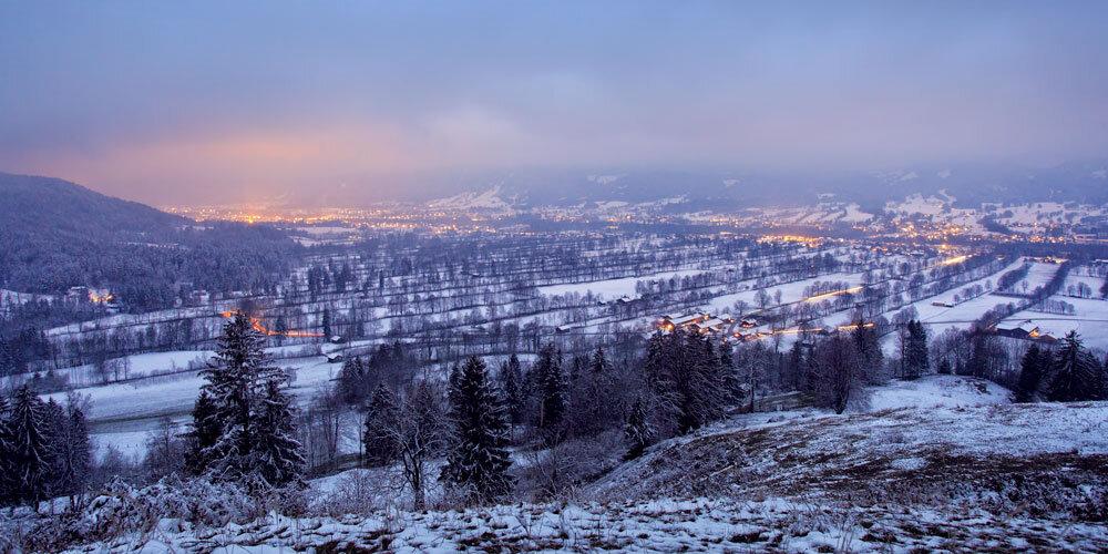 Blick von der Sonntraten über das verschneite Isartal zur Abenddämmerung.